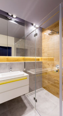 Modern bathroom interior with glass shower cabin, dark gray tiles, mirror and white washbasin