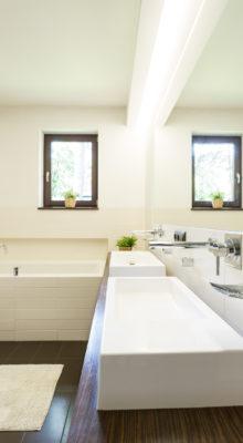Minimalist beige bathroom with two wash basins, bathtub, large wall mirror and wooden details